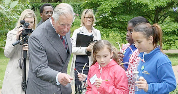 HRH Prince Charles in the Clarence House grounds, with young people holding pooters, at the launch of National Insect Week 2012